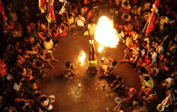 A devotee performs penance with fire on the beginning day of the Danda festival at Sorada village, Bhubaneswar. Devotees inflict physical pain as they perform rituals of penance to appease Shiva.