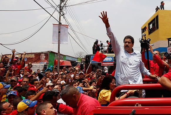 Venezuela`s interim President Nicolas Maduro waves to supporters from the top of a vehicle as he campaigns in a caravan from Sabaneta to Barinas, in Sabaneta, Venezuela.