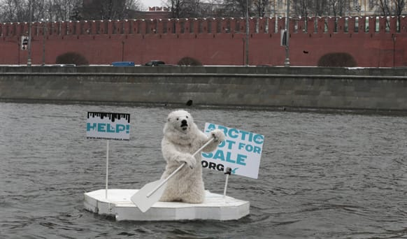 A greenpeace activist dressed as a polar bear sits on a wooden block of ice on the Moskva River protesting against plans of oil companies` drilling in the Arctic, with the Kremlin wall in the background, in Moscow, Russia.