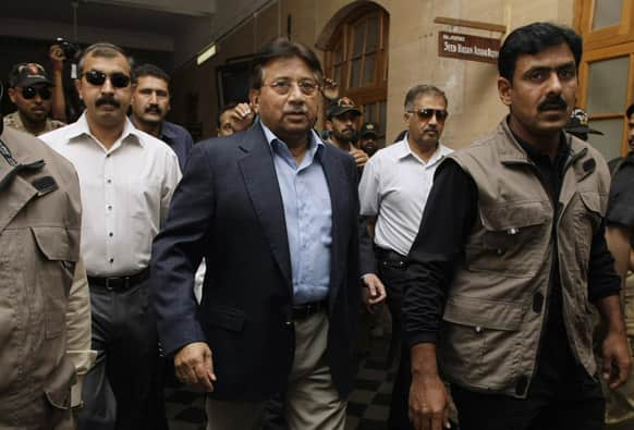 Former Pakistani President Pervez Musharraf, center, surrounded by guards arrives in a court in Karachi, Pakistan.