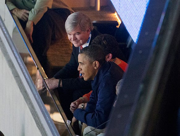 President Barack Obama sits with NCAA President Mark Emmert, top, as they attend the East Regional final of the NCAA men`s college basketball tournament between Syracuse and Marquette, in Washington.