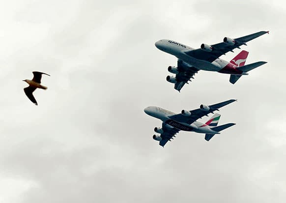 A gull flies near a Qantas, top, and Emirates A380 as they fly in formation over Sydney Harbour in Sydney, Australia.