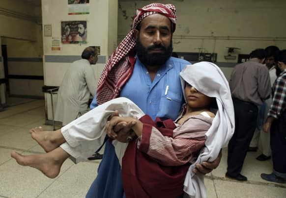 A Pakistani man carries his child who was injured in a grenade attack, inside a local hospital in Karachi, Pakistan.