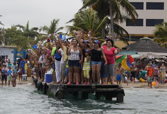 Supporters of opposition presidential candidate Henrique Capriles cheer during a campaign visit by Capriles at Morrocoy Keys, a vacation resort near Chichiriviche, Venezuela.