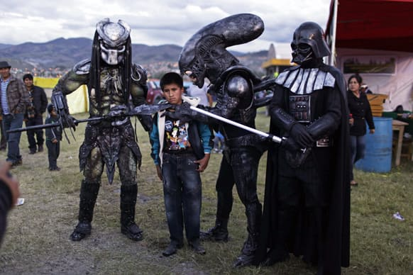 A boy poses for a picture with people wearing costumes of famous sci-fi movies during the Canaan fair which is part of the Holy Week celebrations in Ayacucho, Peru.