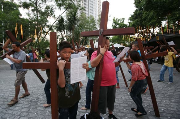 Filipino devotees make the Stations of the Cross as they carry wooden crosses at the Philippine Center of Saint Pio of Pietrelcina, in suburban Quezon city, east of Manila.