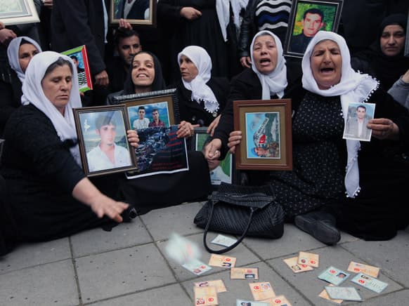 A woman throws her ID card as family members of 34 Turkish Kurdish civilians who were killed in Dec. 2011 in a botched raid in Uludere at Turkey-Iraq border by Turkish military jets that mistook the group for Kurdish rebels based in Iraq.