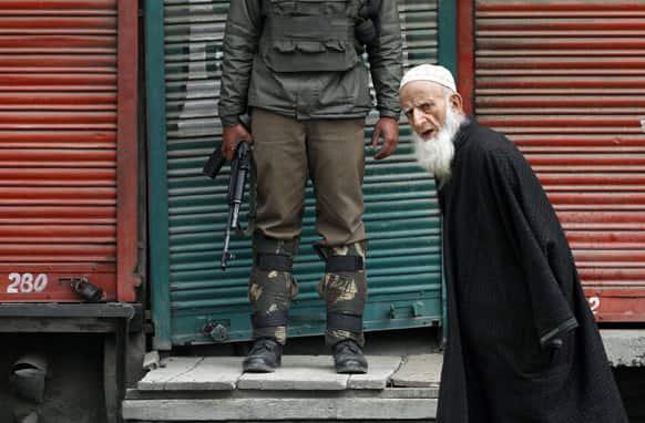An elderly Kashmiri man walks past an Indian paramilitary soldier standing guard at a closed market during a strike in Srinagar.
