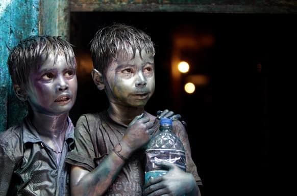 Bangladeshi Hindu children smeared in colors stand at a doorway as they watch Holi festival celebrations in Dhaka.