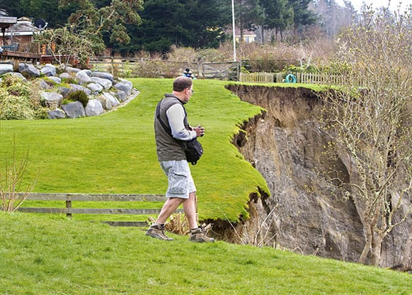 Geologist Terry Swanson from the University of Washington surveys the damage from a landslide on Whidbey Island near Coupeville, Wash.