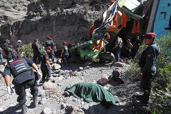 Police officers stand near the dead body of a passenger after a bus crashed in the southern department of Arequipa, Peru. At least 24 people were killed and 18 were injured when the passenger bus plunged 100 meters (328 feet) into a ravine in the Arequipa-Puno road.