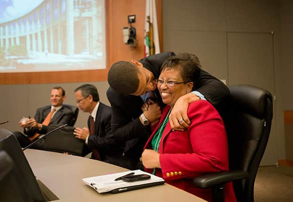 Sacramento Mayor Kevin Johnson gives council member Bonnie Pannell a kiss after her vote in support of the arena financing plan at City Hall in Sacramento, Calif.