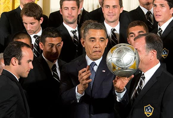 President Barack Obama, center, flanked by LA Galaxy forward Landon Donovan, left, and coach Bruce Arena, right, throws the soccer ball to the crowd during a ceremony in the East Room of the White House in Washington.