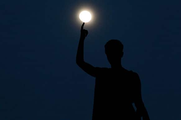 A statue atop a monument representing Cyprus` liberty, seen standing as the moon rises behind, in capital Nicosia, Cyprus.