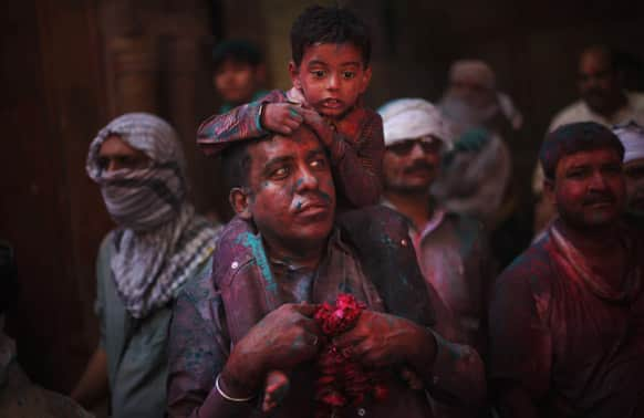 A child sits on the shoulders of a Hindu devotee inside Banke Bihari temple during Holi festival celebrations in Vrindavan.