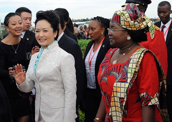 Chinese First Lady, Madame Peng Liyuan, left,, waves as she is accompanied by Tanzanian First Lady, Salma Kikwete, right, at Julius Nyerere International Airport in Dar es Salaam.