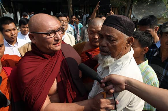 A Myanmar Buddhist monk comforts Muslim refugees, during ethnic unrest between Buddhists and Muslims, as they visit a rescue camp along with Vijay Nambiar, unseen, U.N. Secretary General Ban Ki-moon's special adviser on Myanmar, in Meikhtila, Mandalay division, Yangon.