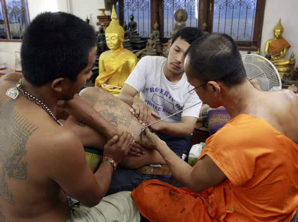 A Buddhist monk, right, uses needle to tattoo the back of a man during the `Wai Kru` or paying honest to masters ceremony at Bang Phra temple in Nakhon Pathom province just south of Bangkok.