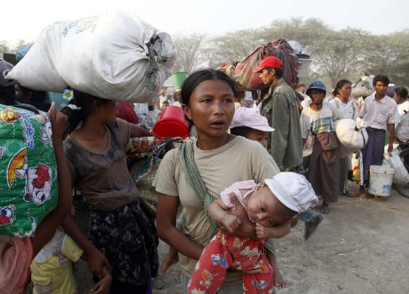 Carrying a child and belongings, Muslims refugees try to move a rescue camp in Meikhtila where ethnic unrest between Buddhists and Muslims, about 550 kilometers (340 miles) north of Yangon, Myanmar.