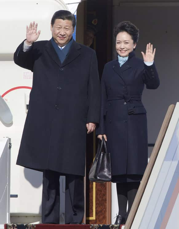 Chinese President Xi Jinping and his wife Peng Liyuan wave upon their arrival to the government airport Vnukovo II, outside Moscow, Russia.