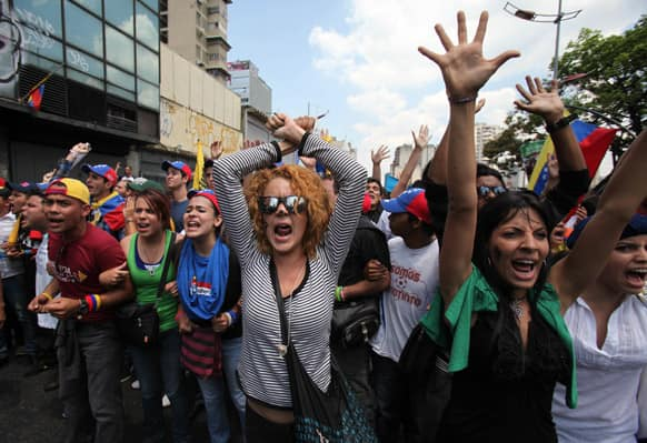 Opposition students shouts slogans against supporters of Venezuela`s late President Hugo Chavez as they are blocked by police from reaching the electoral commission, to keep them and Chavez supporters separated, in Caracas, Venezuela.