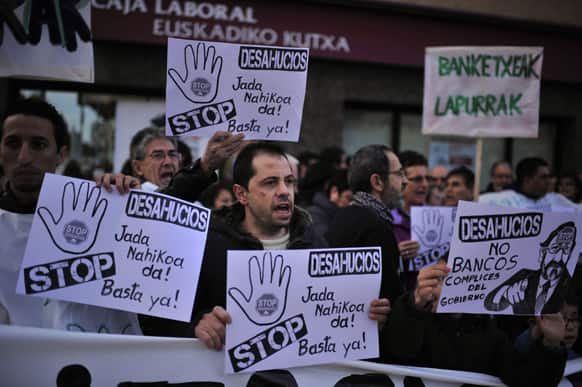 Placards depicting Spanish Prime Minister Mariano Rajoy are carried by people to protest against evictions in front a saving bank in Baranain, near to Pamplona northern Spain.