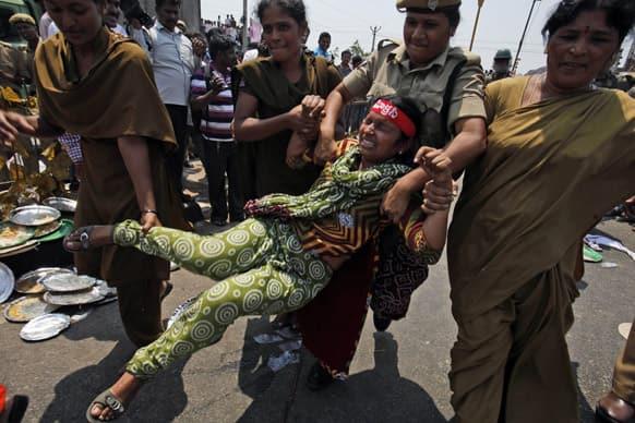 Policewomen detain an activist participating in