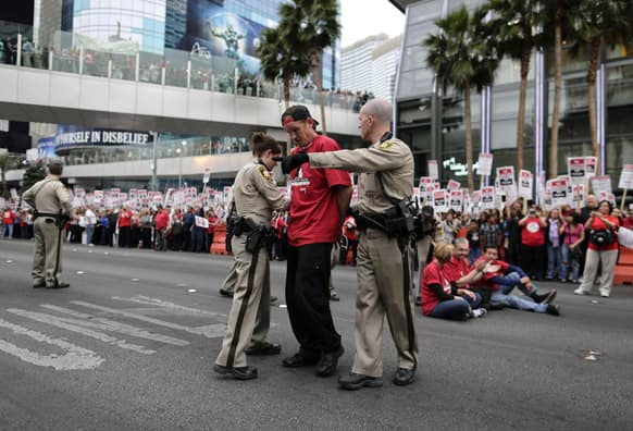 Las Vegas Metropolitan Police officers lead away a protestor during a civil disobedience demonstration by Culinary Union workers outside the Cosmopolitan Hotel-Casino in Las Vegas.