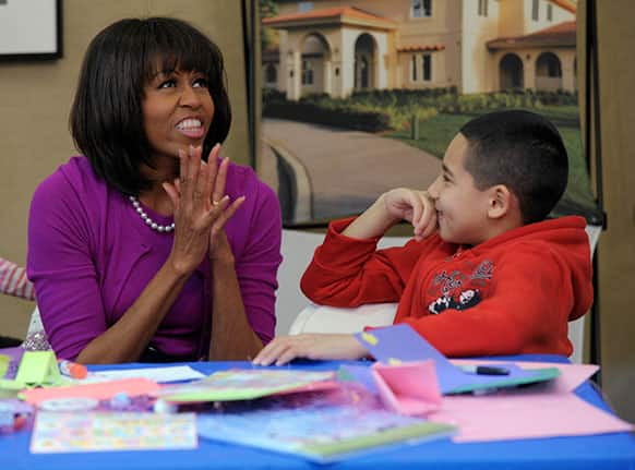First lady Michelle Obama talks with Jorge Ortiz during her visit to the Fisher House, located at Walter Reed National Military Medical Center in Bethesda, Md., for a pre-Easter celebration with military families and children.