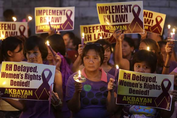 Protesters display placards and lighted candles during a rally at the Philippine Supreme Court in Manila, Philippines to protest the highest court`s issuance of a 120-day status quo ante order or a four-month delay of the implementation of the Reproductive Health Law.
