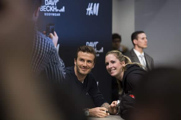 British soccer player David Beckham poses with a woman during an autograph session in a clothing chain shop in Berlin, Germany. Beckham signed pieces of his body wear collection for selected clients.