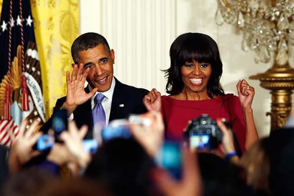 President Barack Obama and first lady Michelle Obama take the stage at a Women`s History Month reception in the East Room at the White House in Washington.