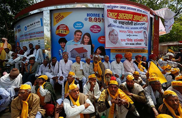 People from the northern Indian community of mainly farmers and herders called `Jat`, sit near a poster promising cheap home loans as they stage a protest near the Indian Parliament in New Delhi.