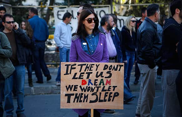 A woman holds a banner during a protest outside of the parliament in Nicosia, Cyprus.