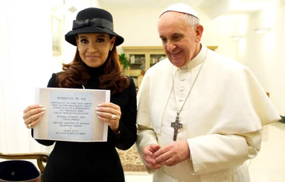 Pope Francis stands by Argentine President Cristina Fernandez showing a picture of a marble plaque commemorating the 1984 peace and friendship treaty between Argentina and Chile as they meet at the Pope`s temporary apartments in the Santa Marta hotel at the Vatican.