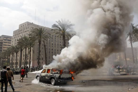 Egyptians extinguish a burning police vehicle, which has been set afire by angry protesters in Tahrir Square, once the epicenter of protests against former President Mubarak, in Cairo.