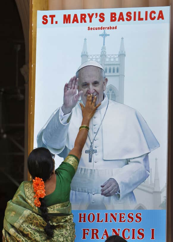 An Indian Catholic devotee touches a portrait of Pope Francis put up at the entrance of Saint Mary`s Basilica in Hyderabad.