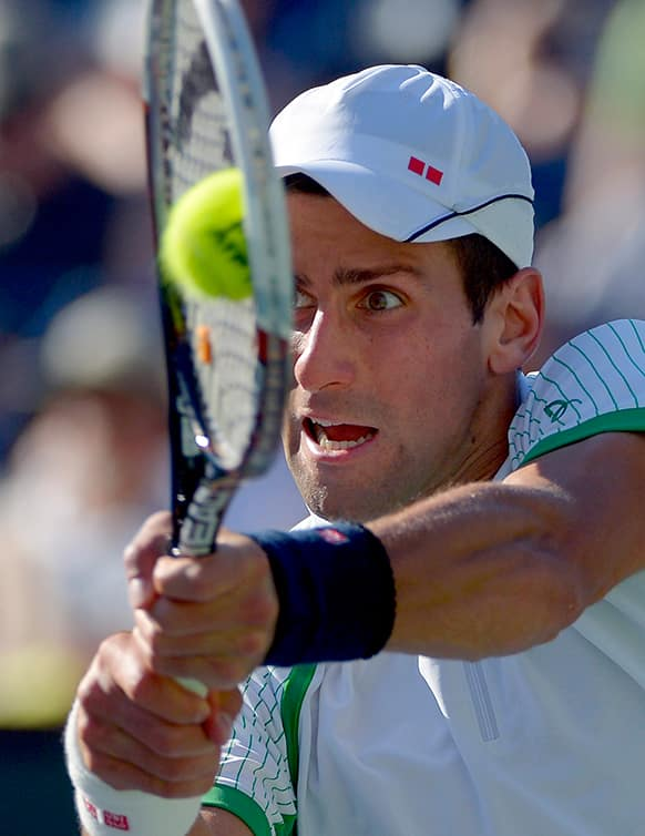 Novak Djokovic, of Serbia, returns a shot to Juan Martin del Potro, of Argentina, in their semifinal match at the BNP Paribas Open tennis tournament.