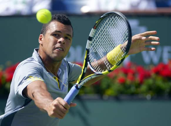 Jo-Wilfried Tsonga, of France, returns a shot to Novak Djokovic, of Serbia, at the BNP Paribas Open tennis tournament.