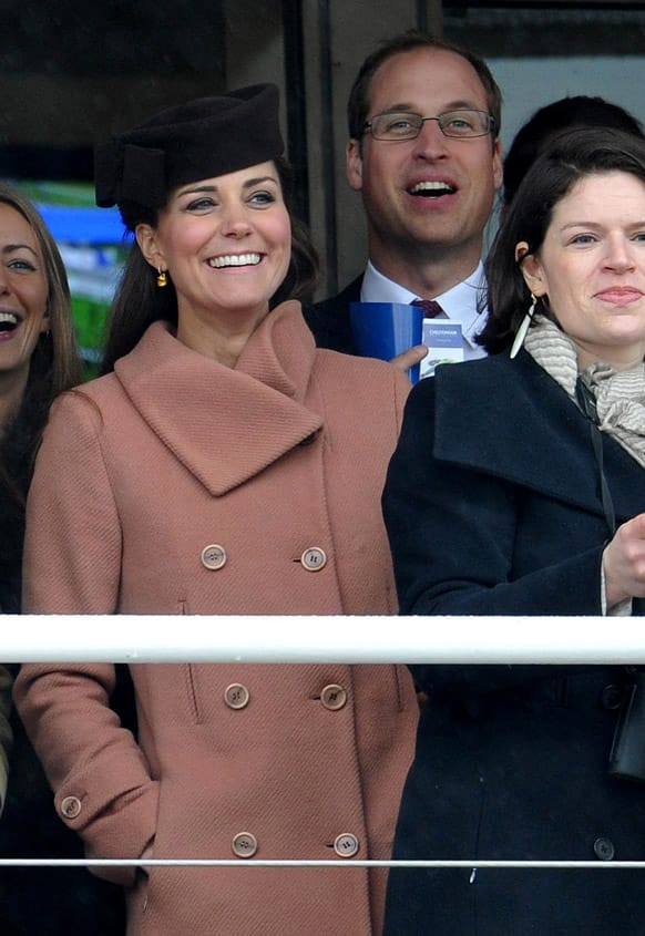 Kate, the Duchess of Cambridge and her husband Prince William watch the first race of the Cheltenham Gold Cup Day at the Cheltenham Racecourse, Gloucestershire, England.
