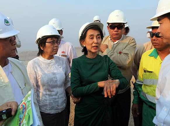 Myanmar`s opposition leader Aung San Suu Kyi talks with officials from Myanmar Yang Tse Copper Limited as she tours a copper mine project in Monywa, north of Yangon.