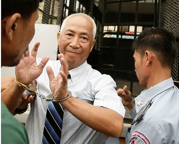 Local radio station owner Mam Sonando, center, is escorted by court security personnel as he enters an appeals court in Phnom Penh, Cambodia.