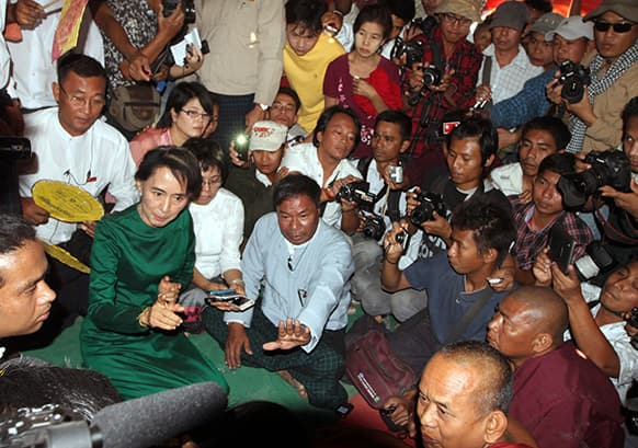 Myanmar opposition leader Aung San Suu Kyi talks to a protester as she pays her respects to Buddhist monks in Tone village, an area near the Letpadaung copper mine project, in Monywa, 760 kilometers (450 miles) north of Yangon, central Myanmar.