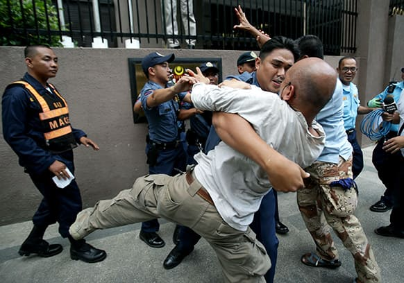 A Filipino policeman prevents activists from touching a sign of the Malaysian Embassy during a rally to call for peace in Sabah at the financial district of Makati, south of Manila, Philippines.