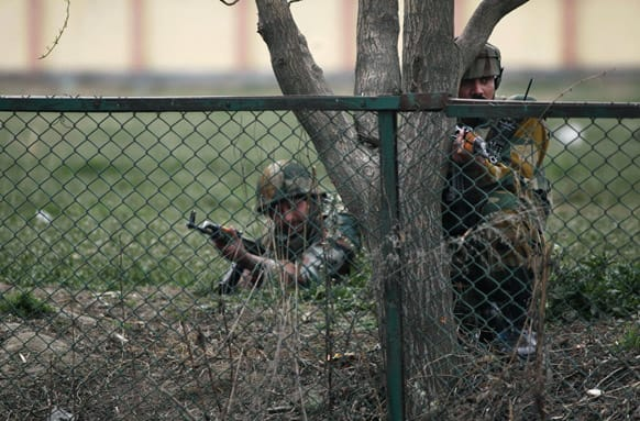Army soldiers take cover during a gunbattle in Srinagar. A team of militants stormed a paramilitary camp Wednesday morning in the capital of Kashmir, leaving five soldiers and two militants dead and 10 more people wounded.
