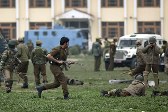 Policemen and paramilitary soldiers react during a gunbattle in Srinagar.