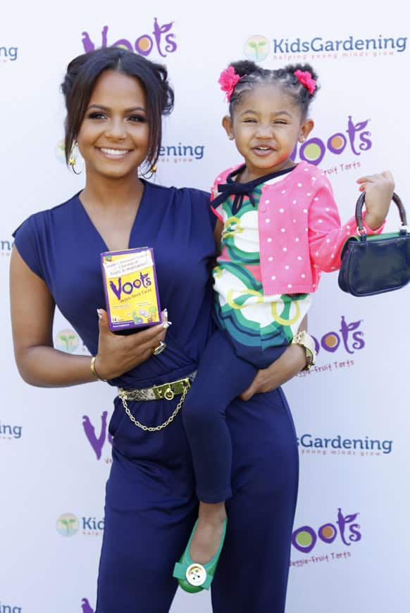 Christina Milian and daughter Violet smile for the camera while posing with Voots Veggie-Fruit tarts, a children`s supplement at the Voots `Get Kids Growing` Garden Workshop, at the Americana at Brand in Glendale, California.