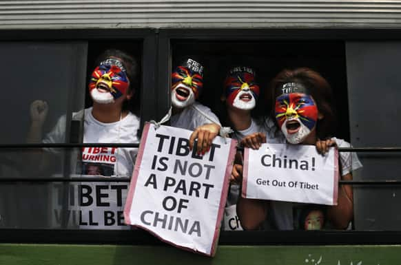 Exiled Tibetan women with their faces painted in the colors of a Tibetan flag shout slogans from inside a bus after they were detained during a protest to mark the anniversary of a failed 1959 uprising against Chinese rule outside the Chinese Embassy in New Delhi.