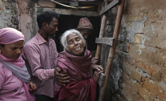 Unidentified relatives of Ram Singh, the man accused of driving the bus on which the 23-year-old student was gang raped in December 2012, walk with Singh`s mother outside the family`s home in New Delhi.