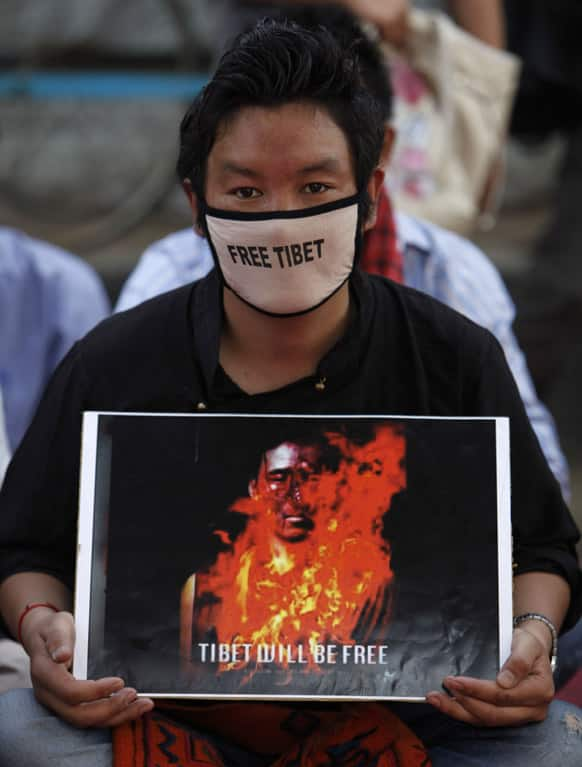An exile Tibetan holds a poster during a sit-in protest in Hyderabad, India, as Tibetans mark the anniversary of a failed 1959 uprising against Chinese rule.